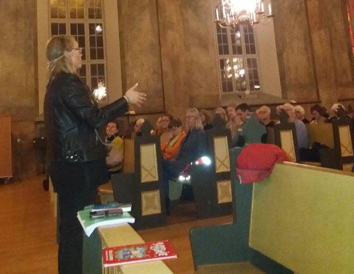 Ulrica står och föreläser, i bakgrunden syns publiken som lyssnar.