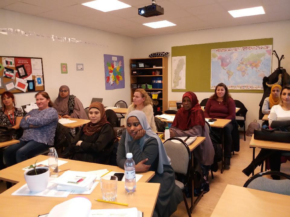Elever på sfi som sitter vid sina bänkar och lyssnar på vad Monica och Margreth har att berätta