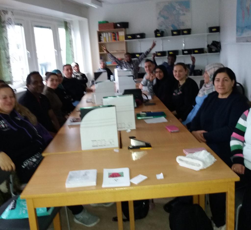 SFI-elever sitter vid ett bord i skolans lokaler